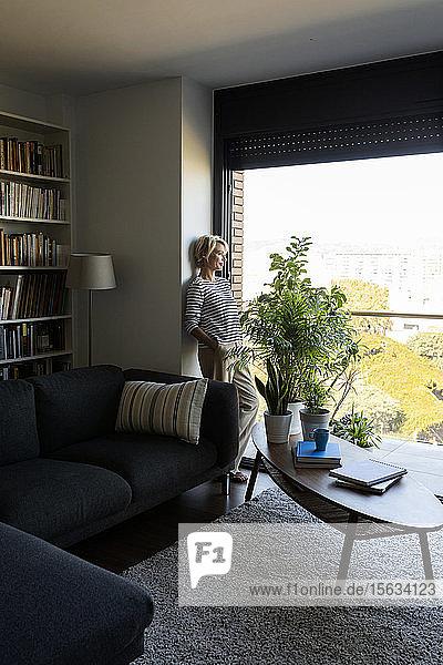Reife Frau steht zu Hause am Fenster im Wohnzimmer und schaut hinaus