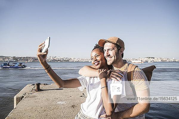 Glückliches junges Paar beim Selfie am Pier am Wasser  Lissabon  Portugal
