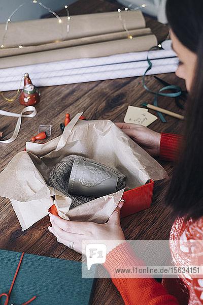 Junge Frau packt Weihnachtsgeschenk ein