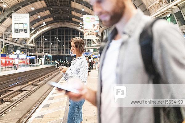 Menschen  die am Bahnhof auf den Zug warten und Smartphones benutzen  Berlin  Deutschland