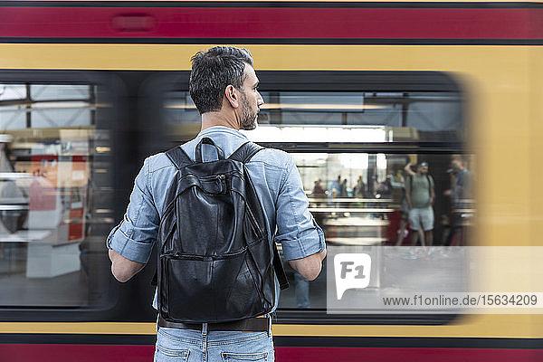 Rückansicht eines Mannes mit Rucksack auf dem Bahnsteig während der Einfahrt des Zuges