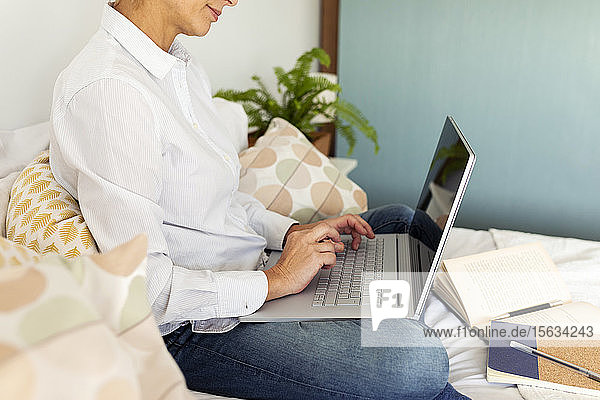 Mature woman sitting on bed at home using laptop