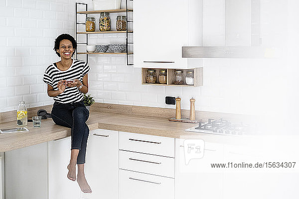 Portrait of happy young woman with smartphone in kitchen at home