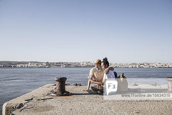 Young couple sitting on pier at the waterfront using cell phone  Lisbon  Portugal