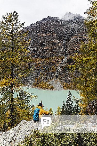 Wanderer sitzt und schaut im Herbst auf den See am Alpenplateau  Sondrio  Italien