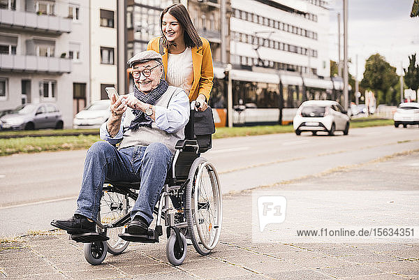 Smiling young woman pushing happy senior man with smartphone in wheelchair