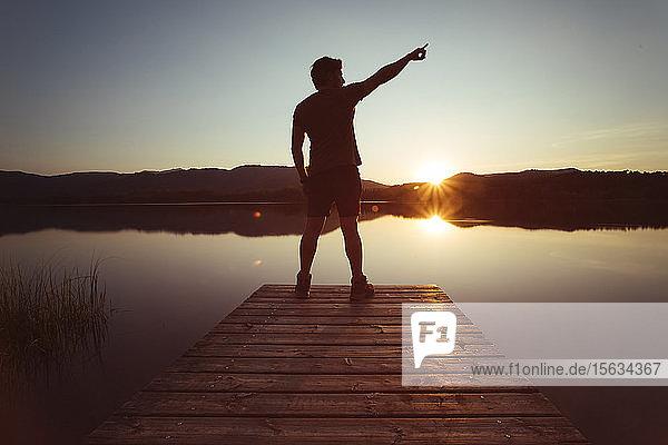 Silhouette eines Mannes  der bei Sonnenuntergang auf einem Holzsteg zum Himmel zeigt
