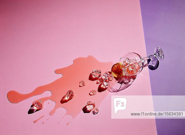 Hochwinkelansicht eines auf einen farbigen Hintergrund gefallenen Getränks