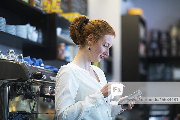 Junge Frau  die im Coffee Shop arbeitet  benutzt Taschenrechner