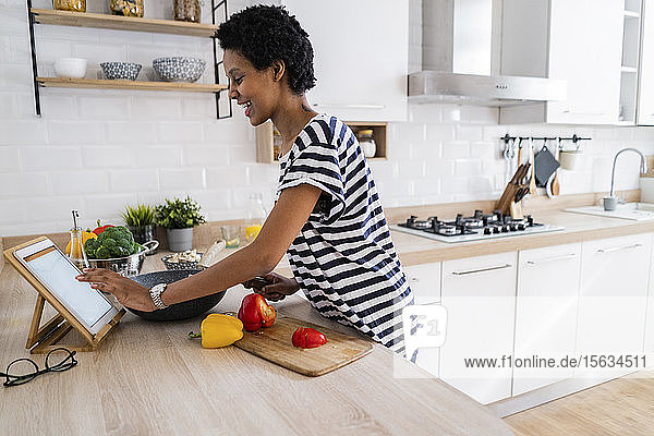 Young woman using tablet cooking in kitchen at home