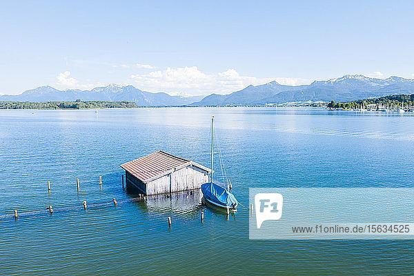 Deutschland  Bayern  Bootshaus im blauen Wasser des Chiemsees mit den Chiemgauer Alpen im Hintergrund