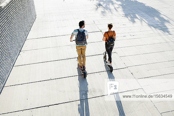 Back view of couple with backpacks riding electric scooters