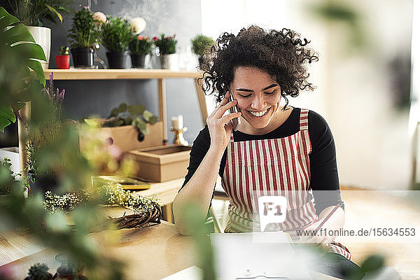 Happy young woman on the phone in a small shop with plants