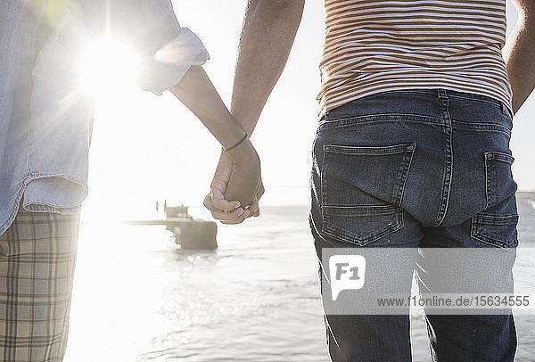 Nahaufnahme eines Paares  das sich bei Sonnenuntergang am Wasser an den Händen hält