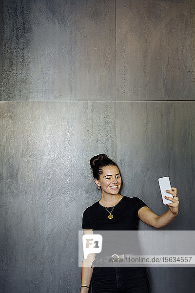 Portrait of happy casual young businesswoman using smartphone in front of a grey wall