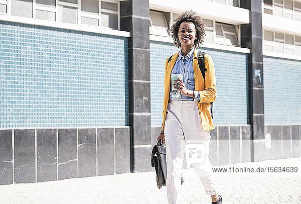 Lächelnde junge Frau in der Stadt unterwegs