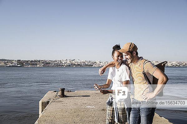 Glückliches junges Paar telefoniert am Pier am Wasser  Lissabon  Portugal