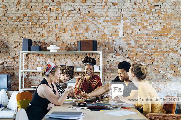 Junge Leute sitzen zusammen am Tisch und machen Mittagspause