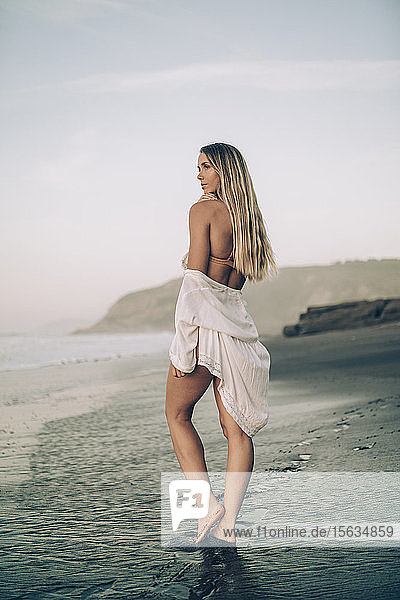 Young blond woman wearing bikini and white dress at the beach in the morning