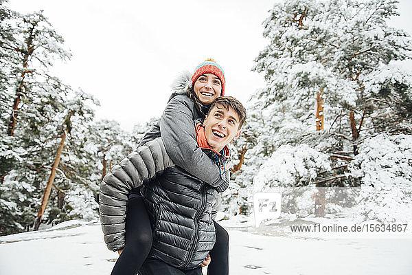 Porträt eines glücklichen jungen Mannes  der seine Freundin im Winterwald Huckepack nimmt
