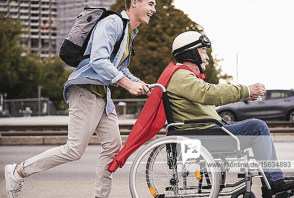 Young man pushing senior man sitting in a wheelchair dressed up as superhero