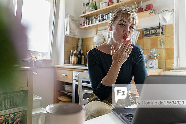 Porträt einer jungen Frau  die in der Küche einen Laptop benutzt und einen Kuss bläst