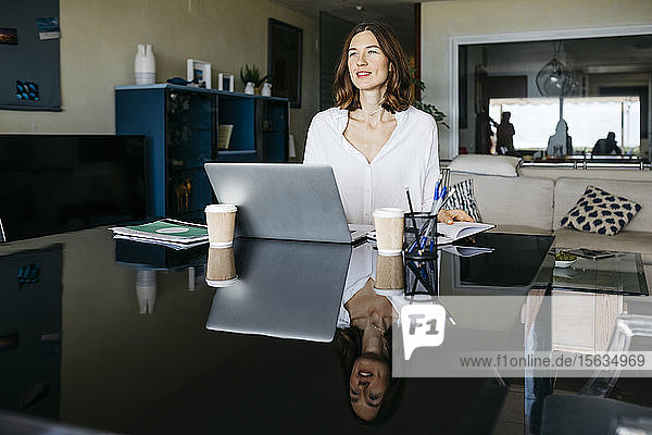 Woman working on table at home with notebook and laptop