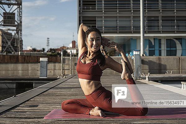 Asiatische Frau praktiziert Yoga auf einem Pier  Schwanenhaltung Asiatische Frau praktiziert Yoga auf einem Pier, Schwanenhaltung