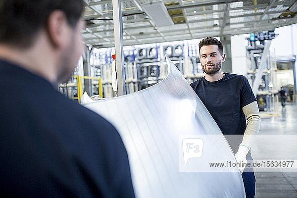 Zwei Kollegen tragen Motorhaube in Autofabrik