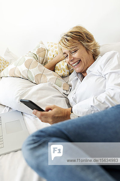 Happy mature woman sitting on bed at home using smartphone