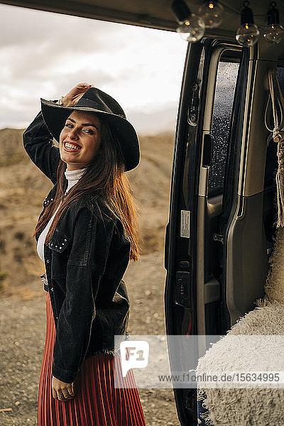 Porträt einer lächelnden jungen Frau in Wüstenlandschaft  die neben einem Wohnmobil steht  Almeria  Andalusien  Spanien