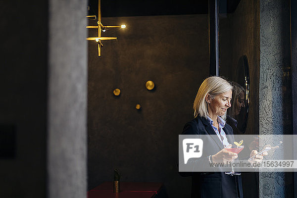 Mature businesswoman taking after work cocktail  using smartphone