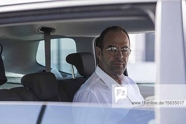 Porträt eines reifen Geschäftsmannes mit Smartphone im Auto