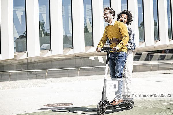 Glückliches junges Paar fährt E-Scooter in der Stadt