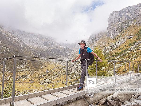 Wanderer  der über einen Steg in den Bergen geht  Naturpark Adamello  Italien