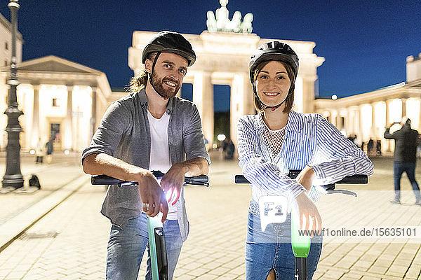 Junges Paar mit Elektrorollern am Brandenburger Tor bei Nacht  Berlin  Deutschland
