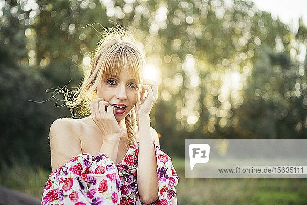 Porträt einer blonden jungen Frau in Sommerkleid mit Blumenmuster im Gegenlicht