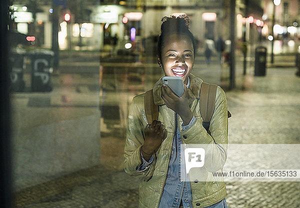 Porträt einer lachenden jungen Frau am Telefon in der Stadt bei Nacht  Lissabon  Portugal
