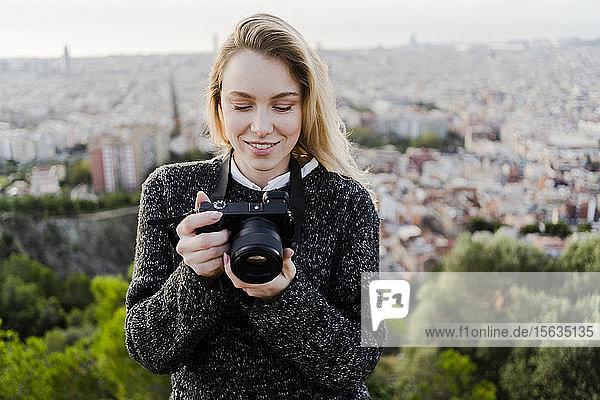 Junge Frau mit Kamera über der Stadt bei Sonnenaufgang,  Barcelona,  Spanien