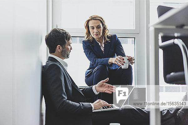 Geschäftsfrau mit einem Geschäftsmann im Büro  der auf dem Boden sitzt und einen Laptop benutzt