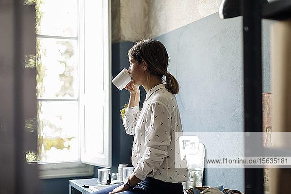 Frau trinkt Kaffee in Büroküche