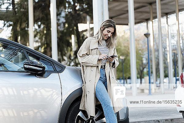 Junge blonde Frau  die ein Smartphone benutzt und sich an ein Auto lehnt