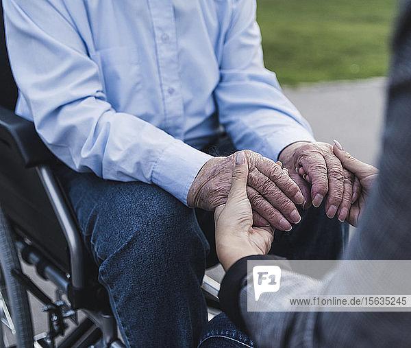 Junge Frau hält Hände eines älteren Mannes  der im Rollstuhl sitzt  Teilansicht