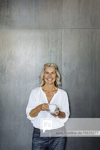 Portrait of a happy casual mature businesswoman standing in front of a grey wall holding coffee cup
