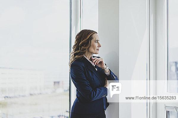 Reife Geschäftsfrau schaut im Büro aus dem Fenster