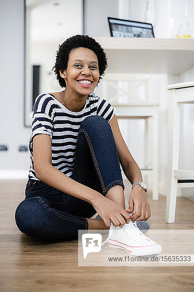 Portrait of happy young woman sitting on the floor at home lacing her sneakers