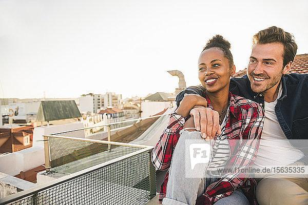 Glückliches  liebevolles junges Paar sitzt abends auf dem Dach