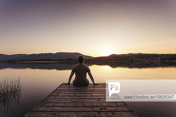 Silhouette eines Mannes  der bei Sonnenuntergang auf einem Holzsteg sitzt