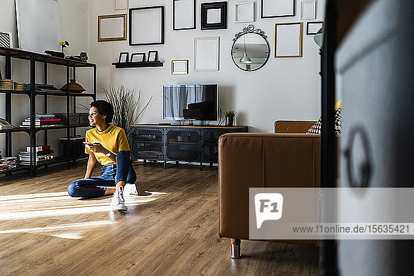 Young woman sitting on the floor at home holding smartphone