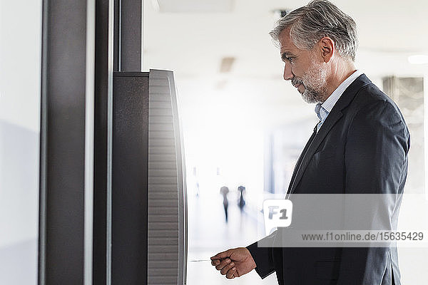 Geschäftsmann  der Geld an einem Geldautomaten abhebt